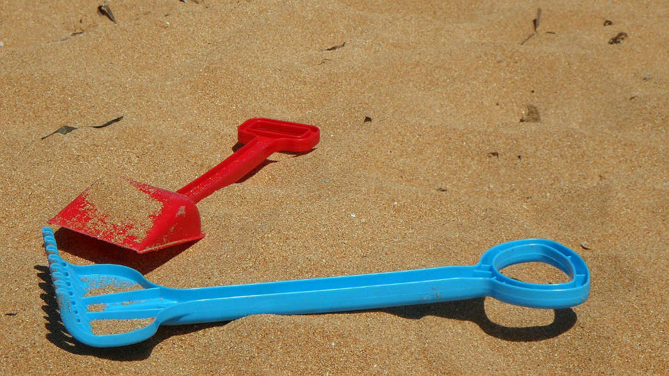 Image of children's shovels on the beach.